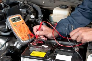 mechanic repairing battery of vehicle